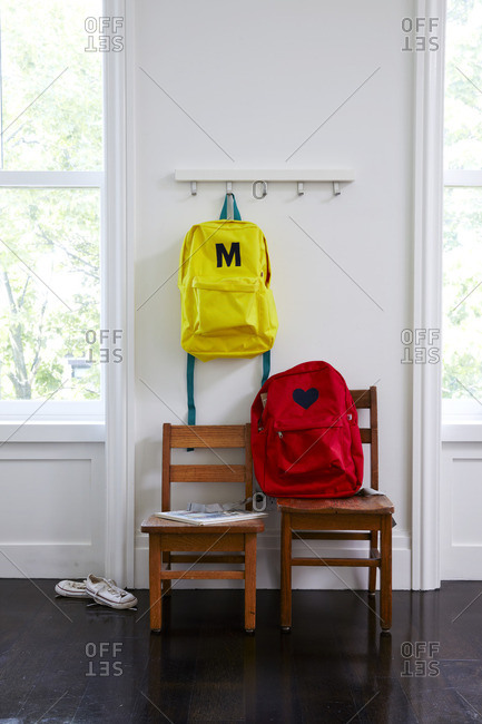 Child's backpacks in room with two wooden chairs