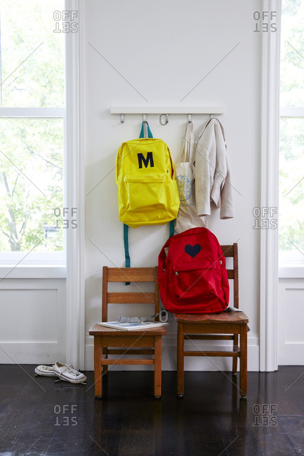 Child's backpacks and coat in room with two wooden chairs