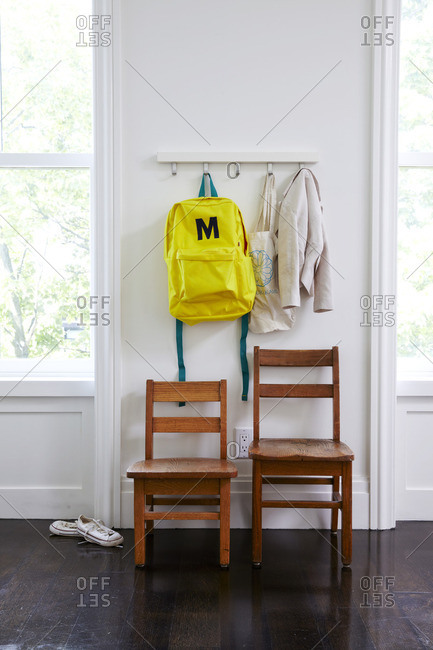Child's backpack and coat hanging on hooks in room with two wooden chairs