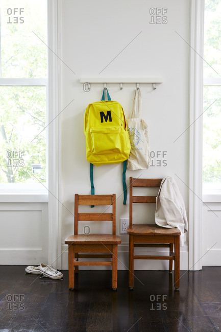 Yellow backpack on a hook and a coat hanging on a wooden chairs