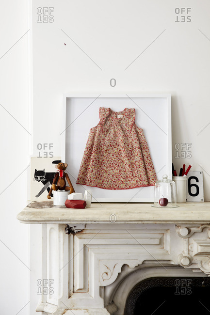 Red dress in a frame on a white mantel