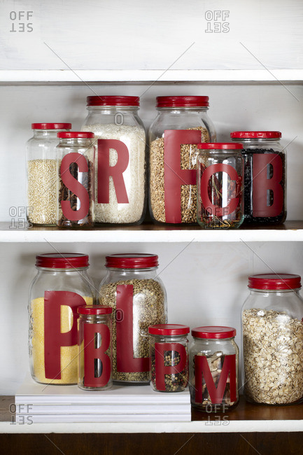 Dry goods in glass jars with letters on shelves