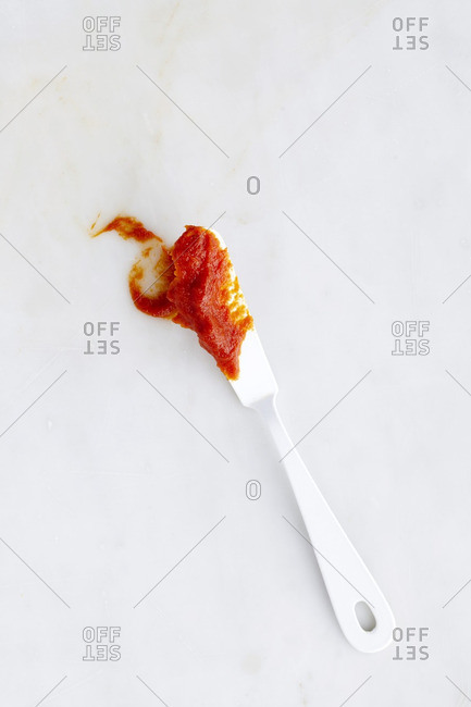 Tomato paste on white knife on white surface