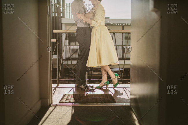 Couple standing on balcony wearing retro attire