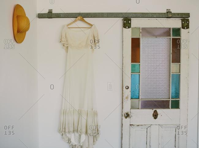 Vintage wedding gown hanging from sliding door