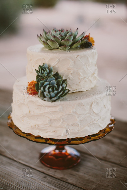 Two tier wedding cake with orange roses and succulents