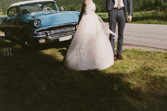 Bride and groom dancing by a classic car