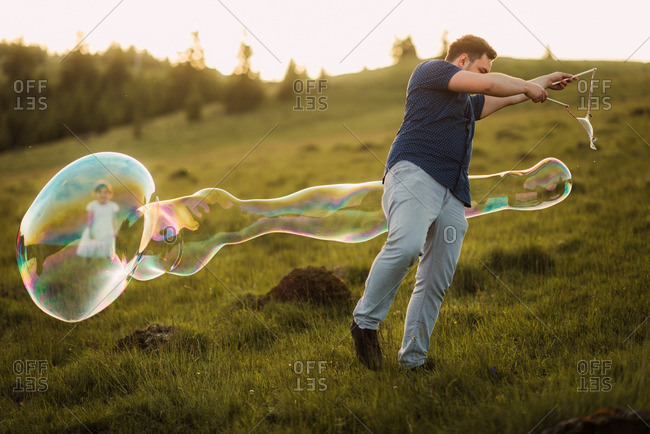 Man and his toddler daughter playing with a large bubble wand on a hillside