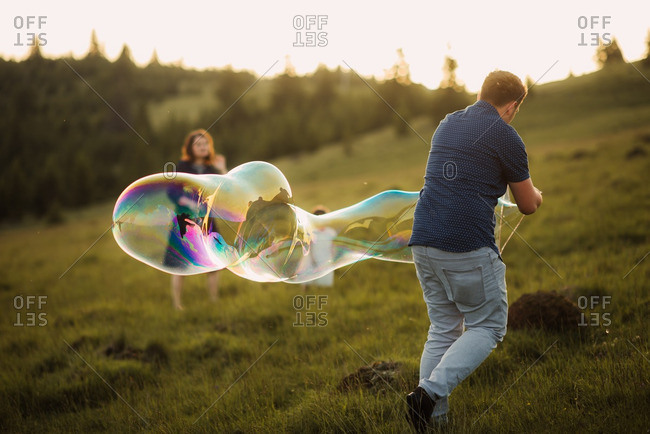 Family playing with a large bubble wand on a mountainside