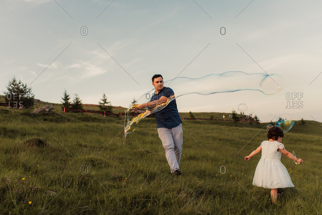 Man making bubbles with a large bubble wand with his daughter