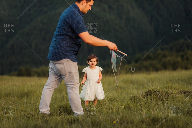 Father and daughter playing with a bubble wand on a mountainside
