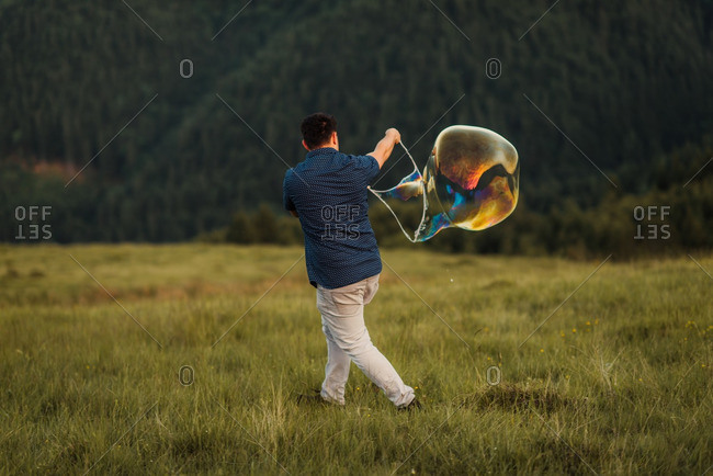 Man on a mountainside making bubbles with a large bubble wand