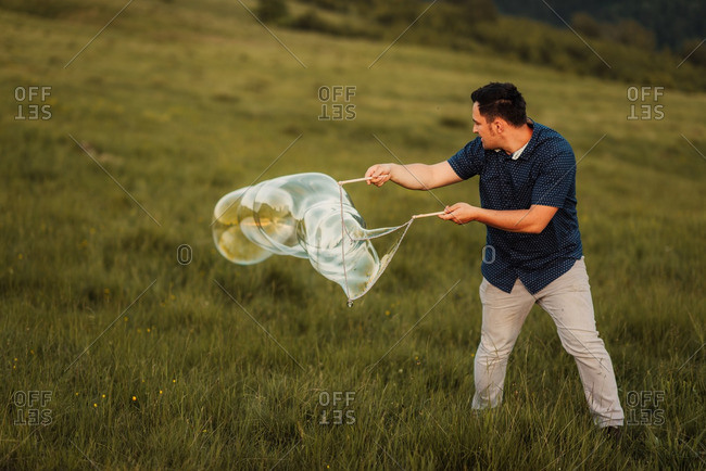 Man making bubbles with a large bubble wand on a mountainside