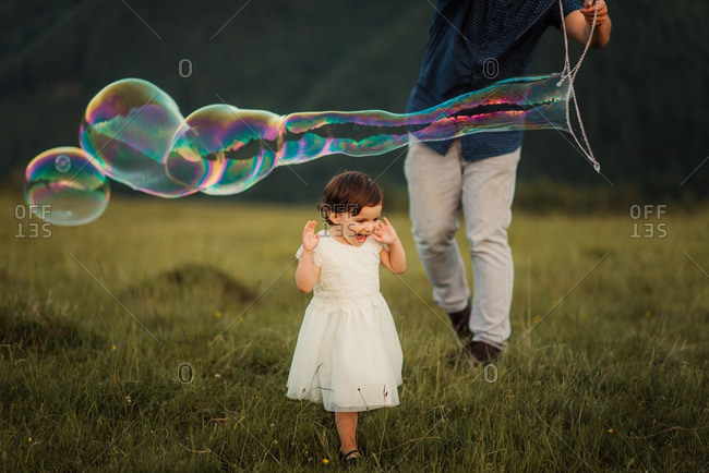 Father waving a bubble wand as his daughter smiles