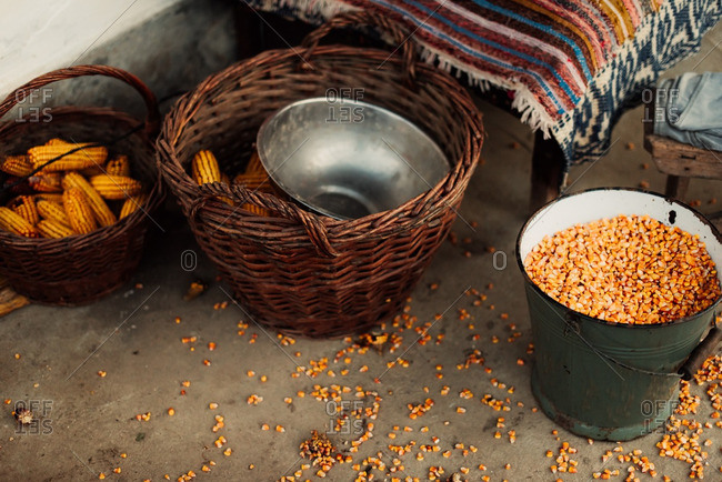 Corn kernels and cobs in rustic buckets and baskets