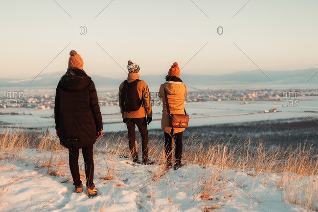 Three people standing on a snowy mountainside overlooking the valley below