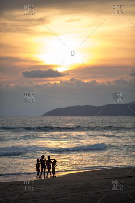 Children standing on a beach at sunset