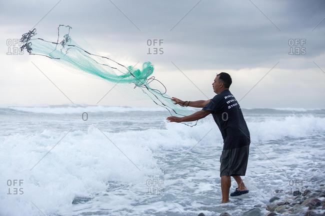 Man casting net into fierce waves