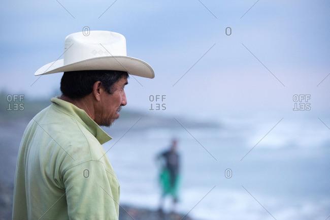 Profile view of a Hispanic man wearing a hat