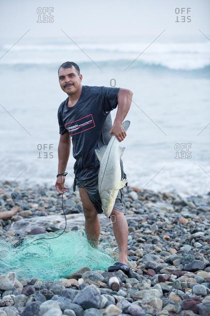Man holding large fish on the seashore