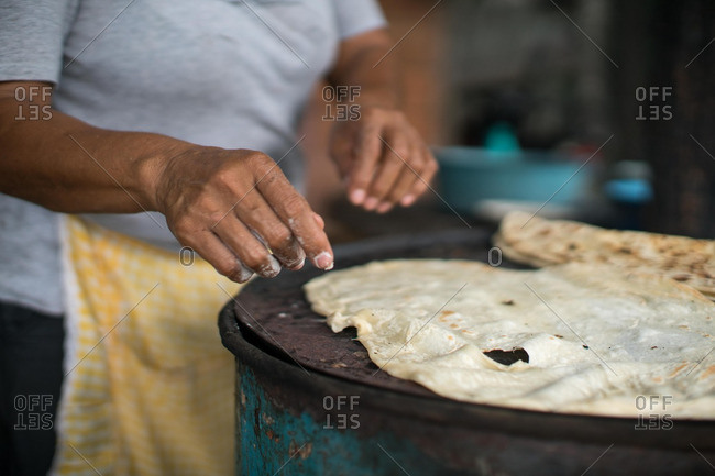 Person cooking flatbread on a grill