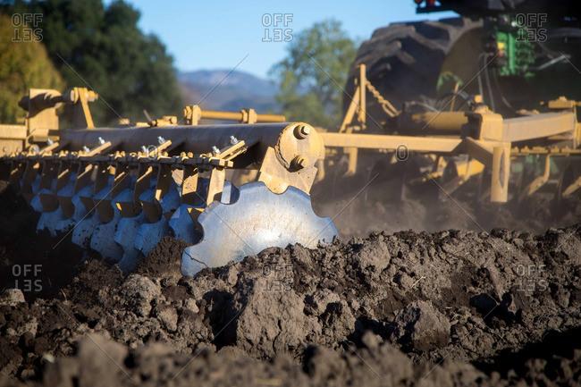Tiller turning dirt in field