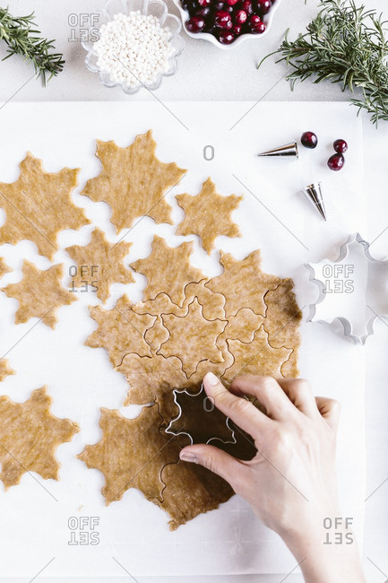 Woman using a snowflake cutter to press into cookie dough