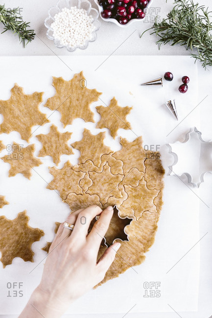 Woman cutting snowflake-shaped cookies in dough