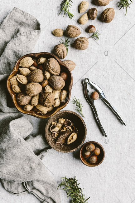 Overhead view of a selection of nuts in bowl with nutcracker