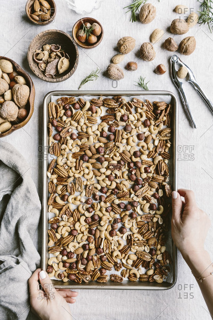 Woman with a tray of mixed nuts for toasting in the oven