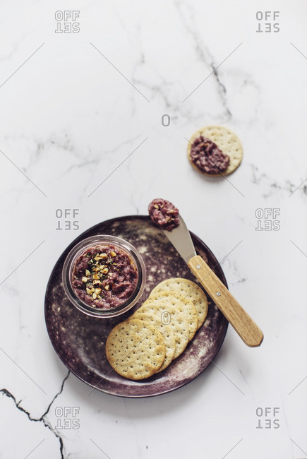 Homemade red chicory pesto in a jar with crackers