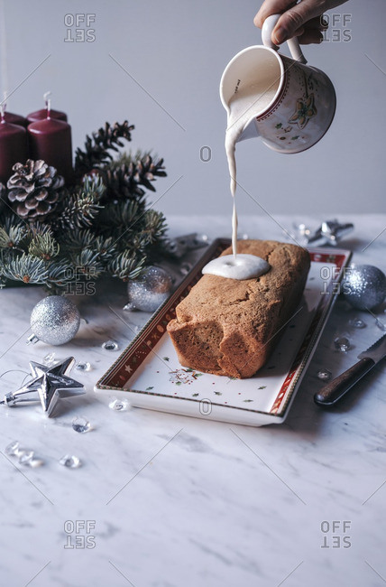 Pouring icing over Christmas cranberry pound cake