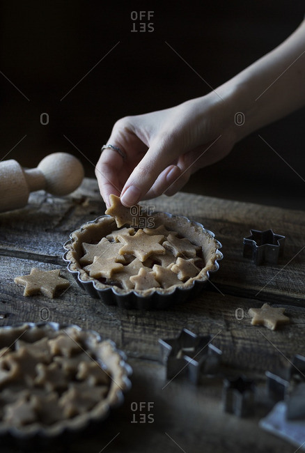 Woman placing dough cut outs of stars