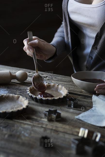 Woman feeling tart shells with jam