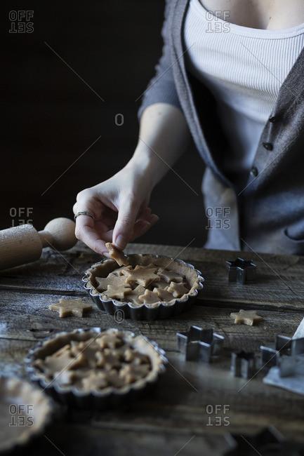Woman putting dough stars on top of jam tart