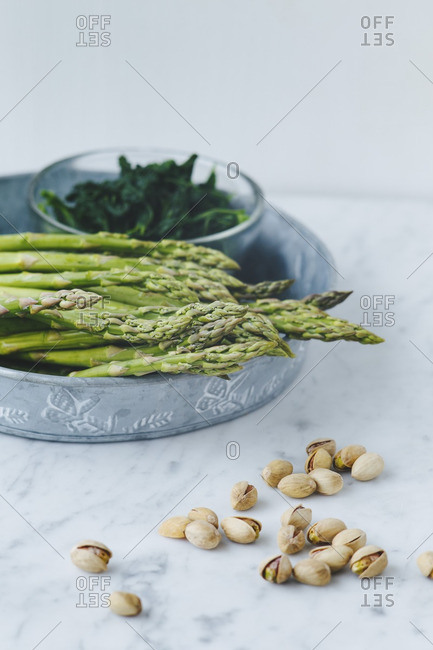 Asparagus and spinach with pistachios on marble counter