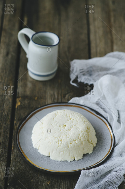 Handmade ricotta on wooden table with cheesecloth