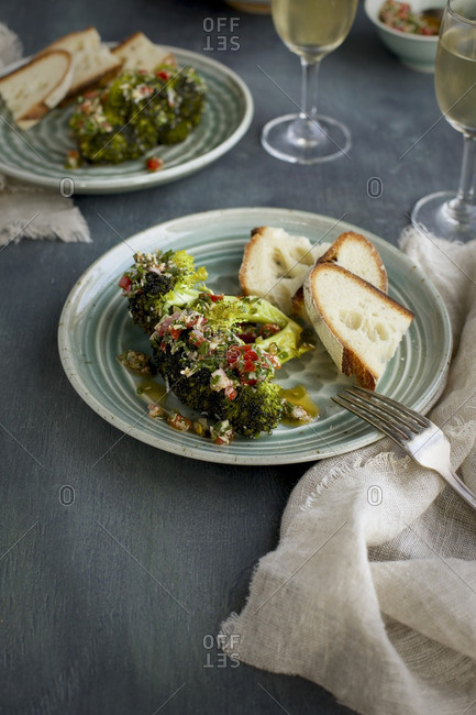 Dishes of roasted broccoli served with bread and white wine
