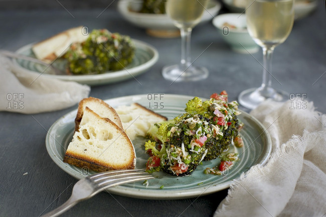 Plates of roasted broccoli with tomatoes and cheese served with bread and white wine