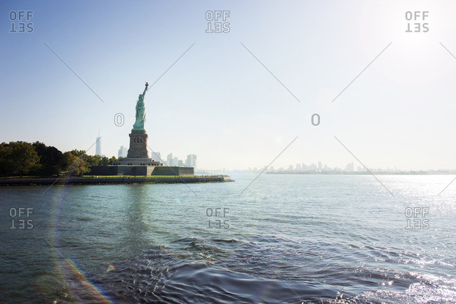Statue of Liberty on island against clear blue sky