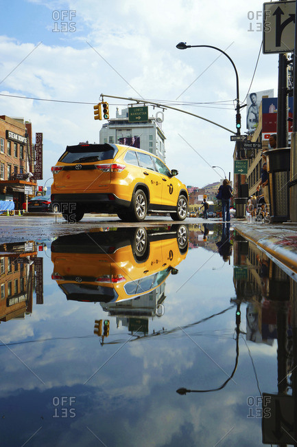 USA, New York, New York City - July 7, 2015: Taxi on wet road reflecting in puddle