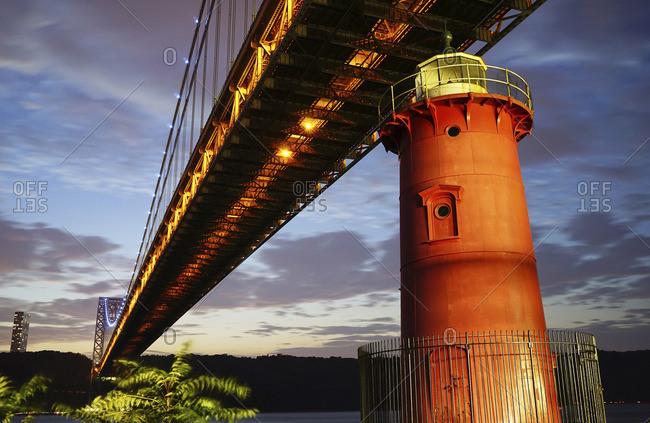George Washington Bridge over red lighthouse at dusk