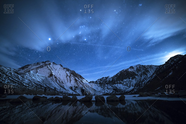 Scenic view of snowcapped mountain against starry sky