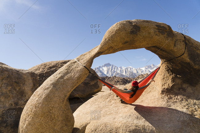 Woman relaxing on hammock hanging from rock formation