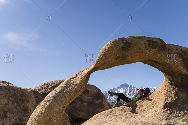 Female hiker lying on rock formation against blue sky