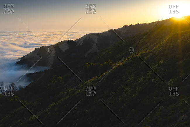 Scenic view of mountain by cloudscape during sunset