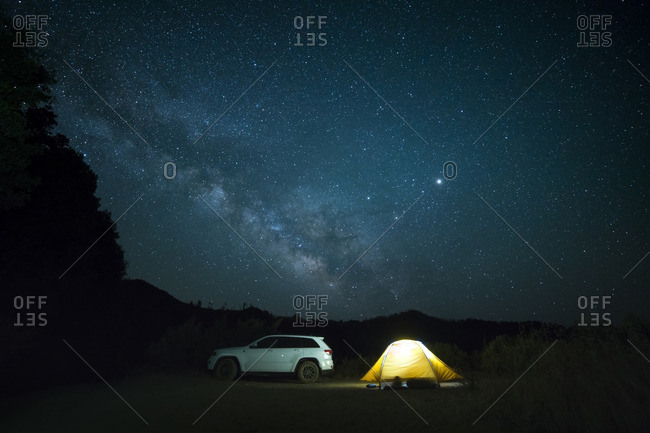 Car parked by illuminated tent against starry sky at night