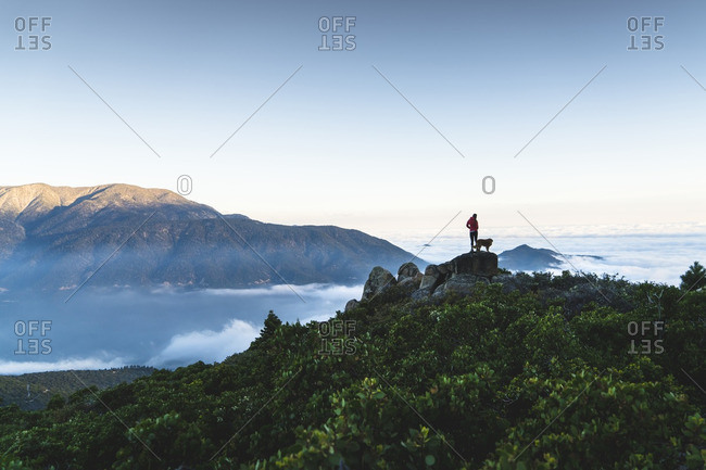 Distant view of woman with dog standing on top of mountain by cloudscape