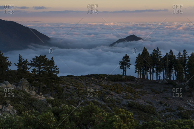 Scenic view of cloudscape by mountain during sunset