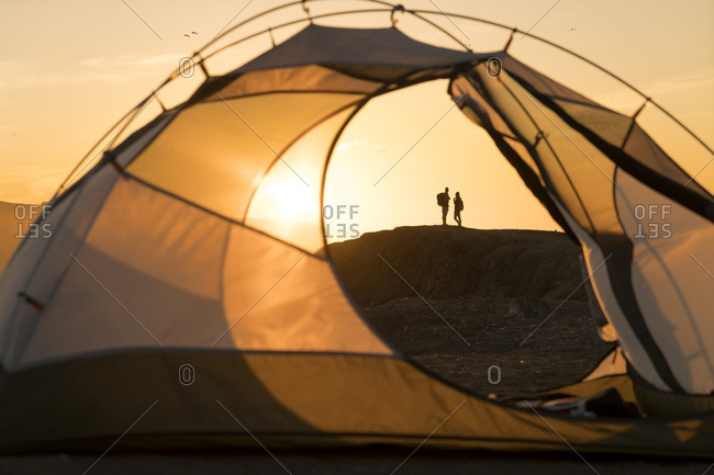 Distant view of couple standing on rock formation seen through tent during sunset
